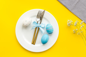 Easter table decoration. Plate, cutlery, painted eggs and dry white flowers, tablecloth on yellow background top view