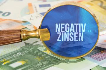 Euro Geldscheine, eine Lupe und Negativzins