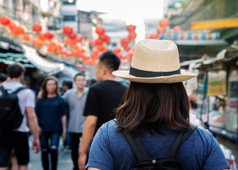 Beautiful woman traveler holding location map while looking for some direction in street food china town.