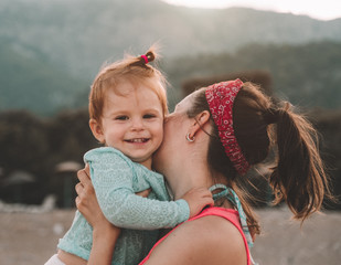 Young mother with her little baby girl have fun sitting on a beach in summer day at sunset over mountains. Happy family concept. Happy childhood