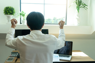 young businessman sit and look to the computer watch stock market.