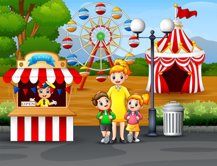 Happy kids and their parent having fun in an amusement park