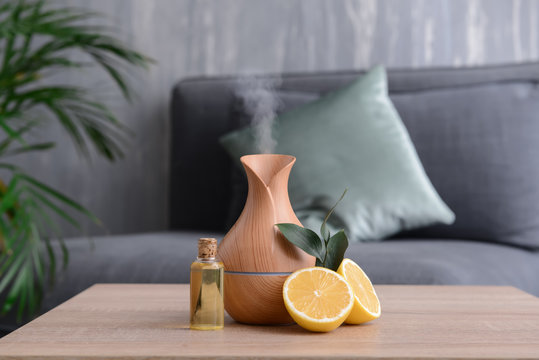 Aroma oil diffuser and citrus fruit on table in room