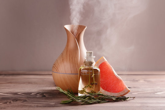 Aroma oil diffuser, rosemary and grapefruit on table