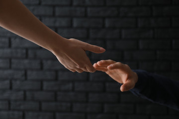Woman giving hand to depressed man against dark background. Suicide prevention concept