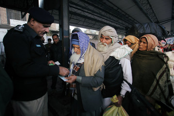 Passengers from India with their belongings, pass through a ticket control before they leave by Samjhauta Express train which was temporarily suspended after Pakistan shot down two Indian military aircrafts, at the railway station in Lahore,
