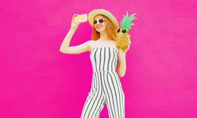 Stylish happy smiling woman with pineapple taking selfie picture by phone in summer round hat, white striped jumpsuit on colorful pink background