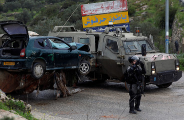 Israeli border policeman takes pictures as a damaged car is removed at the scene of an incident near Ramallah, in the Israeli-occupied West Bank