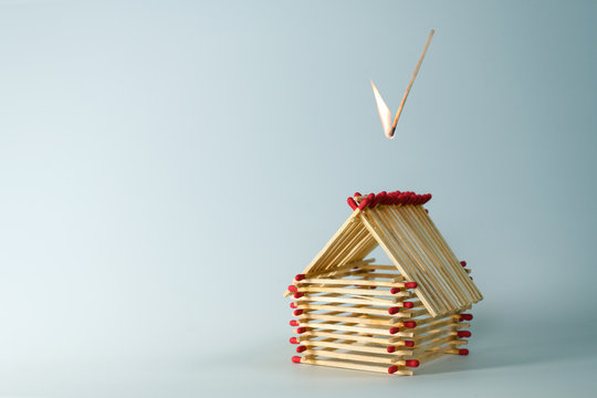 inflamed match is falling on a house built of matches, light blue background with large copy space, insurance concept for real estate investment risk or life fate