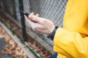 Close-up of mobile phone in hand. Man in yellow raincoat on the street
