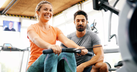 Personal trainer helping young woman reach goals