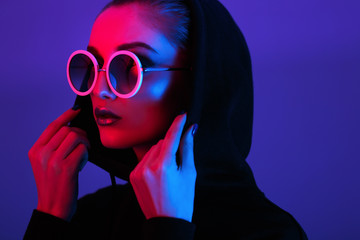 Portrait of fashion young girl in a black sweater with a hood and round sunglasses in red and blue neon light in the studio Wall mural