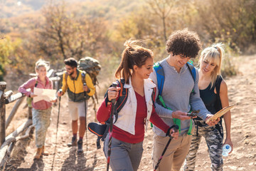 Friends looking at map and compass. Man with curly hair holding map and compass while women looking. Hiking at autumn concept.