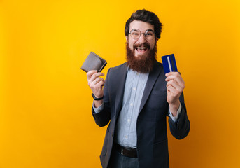 Image of excited bearded businessman holding old wallet and new credit card over yellow background