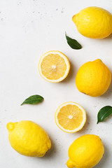 Ripe lemons flat lay with leaves on white background