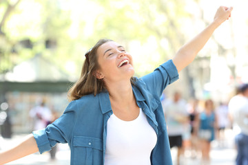Excited girl celebrating success in the street