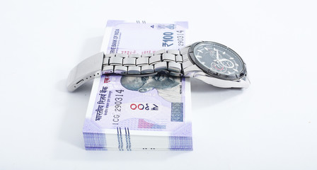 Portrait of new 100 rupees note with watch. Isolated on the white background.