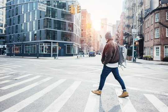 Man with mobile phone walking on the city street and crossing the road