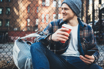 Handsome man sitting on the city urban street resting with cup of hot coffee and using mobile phone