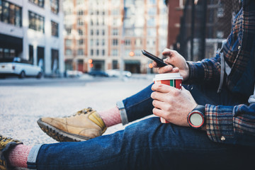 Casual man sitting on the street sidewalk resting with cup of hot coffee and using mobile phone. Close-up