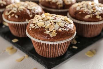 Tasty almond muffins on slate plate, closeup