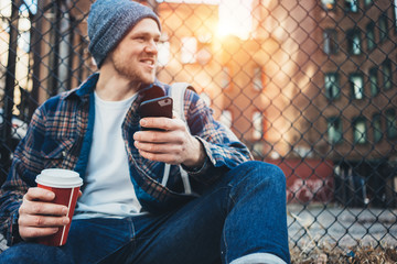 Smiling man sitting on the city street resting with cup of hot coffee and using mobile phone
