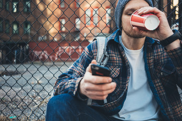Handsome man sitting on the city street drinking cup of hot coffee and using mobile phone