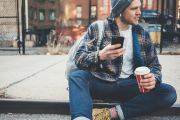 Casual man sitting on the city street resting with cup of hot coffee and talking on mobile phone using wireless earphones
