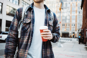 Casual man walking on the street sidewalk with cup of hot coffee. Close-up