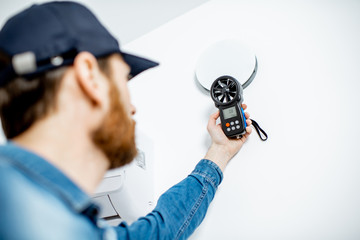 Fototapeta Handyman checking the speed of air ventilation with measuring tool on the white wall background obraz