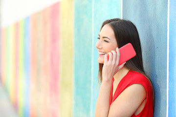 Fashion girl talking on phone leaning in a colorful wall