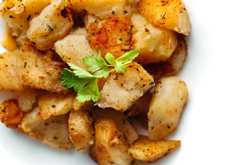 Delicious gold fried potato with herbs on big rounded white plate. Tasty rustic dish for dinner on white background.