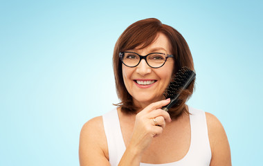 beauty, haircare and old people concept - portrait of smiling senior woman in glasses brushing hair by hairbrush over blue background