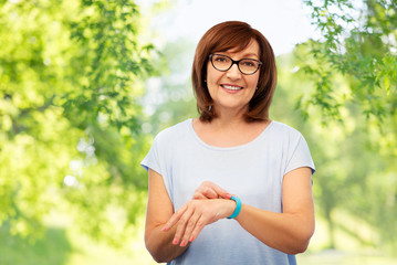 sport, old people and technology concept - smiling senior woman with fitness tracker over green natural background