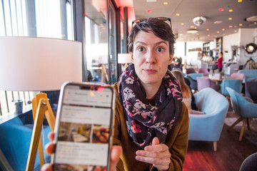 Portrait of a beautiful young woman in warm clothes sitting in cafe and showing her smartphone, blurred background, head and shoulders