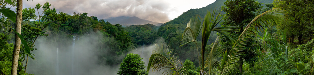 Recess Fitting Forest river Aerial over Sekumpul waterfall surrounded by dense rainforest and mountains shrouded in mist at sunrise, Bali, Indonesia panoramic