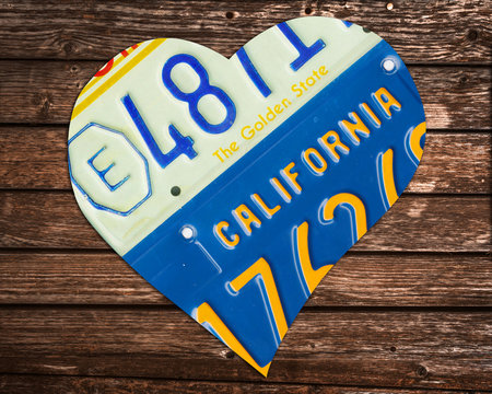 California state license plates in the shape of a heart on wood background