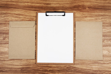 Clipboard with white sheet and brown envelope on wooden table