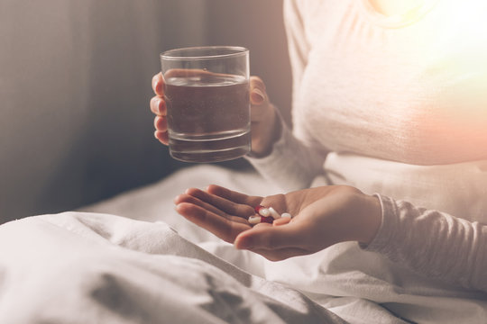 Ill woman in hospital bed take pills