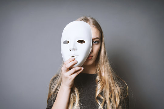 teen girl hiding her face behind mask - identity or personality concept