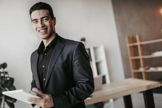 Cheerful nice young latino businessman smile to camera. He stand in office room and hold white tablet. Guy wear black suit