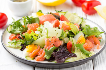 Salad with salmon, egg and vegetables (cherry tomatoes, cucumber, lettuce), delicious light lunch, healthy food