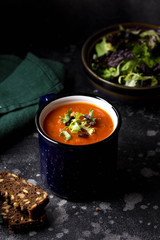 Orange vegetable cream soup in mug (tomato, carrot, lentil, pumpkin), delicious hot homemade lunch in cup. Dark background