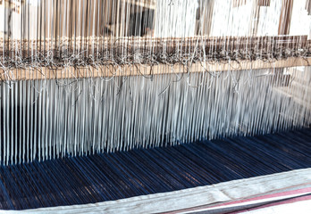 Detail of an old traditional vintage weaving loom with many cotton strings tied to a wooden frame as a professional handwork manufacturing tool for handmade weave production in a textile workshop