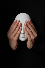 Girl's hands close eyes of plaster mask face on a black background. See no evil. Concept three wise monkeys.
