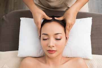 Fototapeta Ayurvedic Head Massage Therapy on facial forehead Master Chakra Point of Mix Race Caucasian Asian woman, Therapist Spa body woman hands treatment on customer to increase circulation release tension