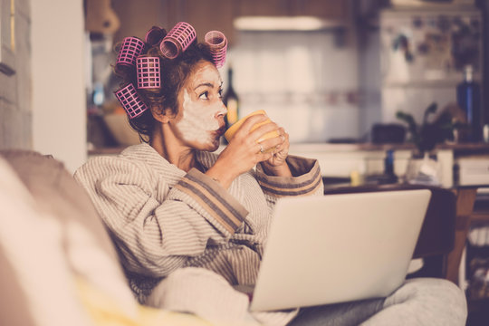Funny housewife at home with pink curlers drinking a cup of tea while use a laptop on the sofa - technology and daily lifestyle at home - vintage filter colors and middle age lady enjoying