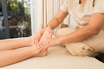 Professional Asian Therapist twist and massage spa on foot of customer to release stress relax muscle pain or injury. Physiotherapist pressing hard fingers thumb on specific spots of female palm feets