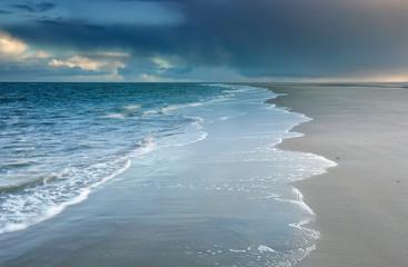 North sea beach at cloudy rainy weather Fotobehang