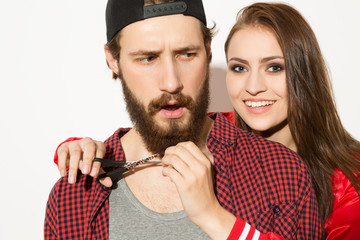 Funny romance. Close up shot of hipster female holding scissors near the beard of her boyfriend laughing.